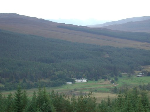 Image:  a long distance shot of a house in the middle of the Scottish Highlands