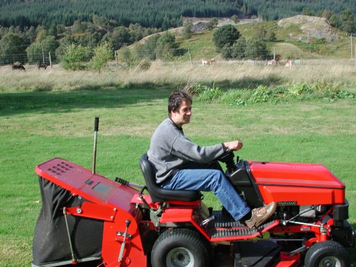 Image:  me driving a ride-on lawnmower in the grounds of the house